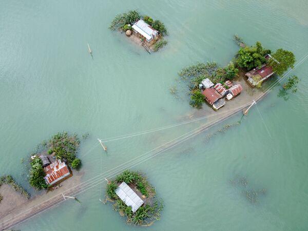 En julio en varios países de Asia del Sur se produjeron fuertes inundaciones. En China 140 millones de personas murieron y desaparecieron en 27 provincias. En Bangladesh las lluvias monzónicas inundaron más de un tercio del territorio del país. En la foto: el pueblo inundado Sunamganj. - Sputnik Mundo