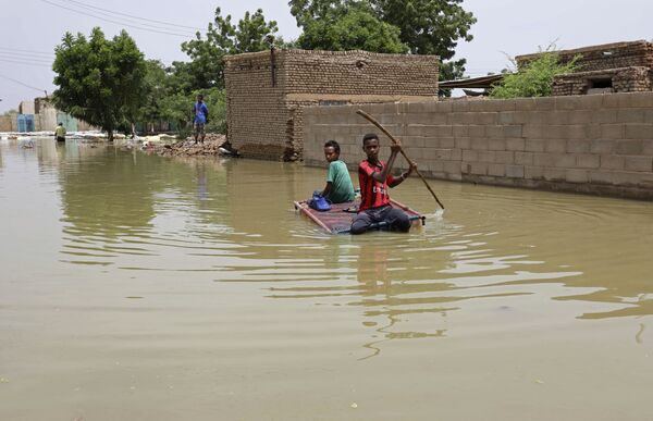 Las abundantes lluvias continuas en septiembre causaron inundaciones devastadoras en 16 provincias de Sudán. Se cobraron la vida de unas 100 personas y destruyeron más de 100.000 viviendas. En la foto: unos adolescentes navegan en una balsa por una calle inundada en la ciudad de Salmania. - Sputnik Mundo