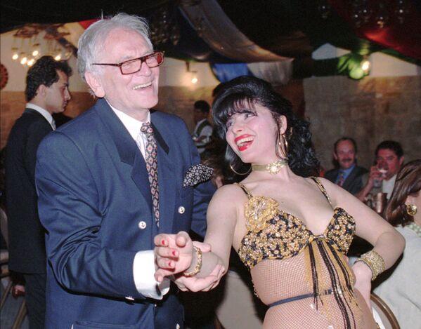 En 1968, Cardin comenzó a producir artículos que no estaban vinculados con el mundo de la moda, como la porcelana. Era un gran aficionado a los inmuebles y propietario de varios edificios ubicados en el VIII Distrito de París, a las afueras del Palacio del Elíseo. En la foto: Cardin junto a una bailarina en el hotel Taybet de Petra (Jordania), en 1996. - Sputnik Mundo