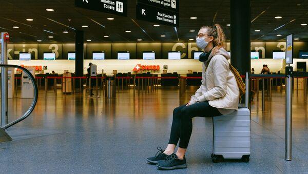 Una mujer en mascarilla en el aeropuerto - Sputnik Mundo