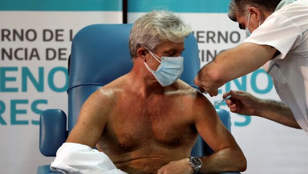 El doctor Emilio Macia, de 52 años, recibe la vacuna contra el coronavirus Sputnik V en el hospital de Avellaneda de Buenos Aires (Argentina), el 29 de diciembre del 2020 - Sputnik Mundo