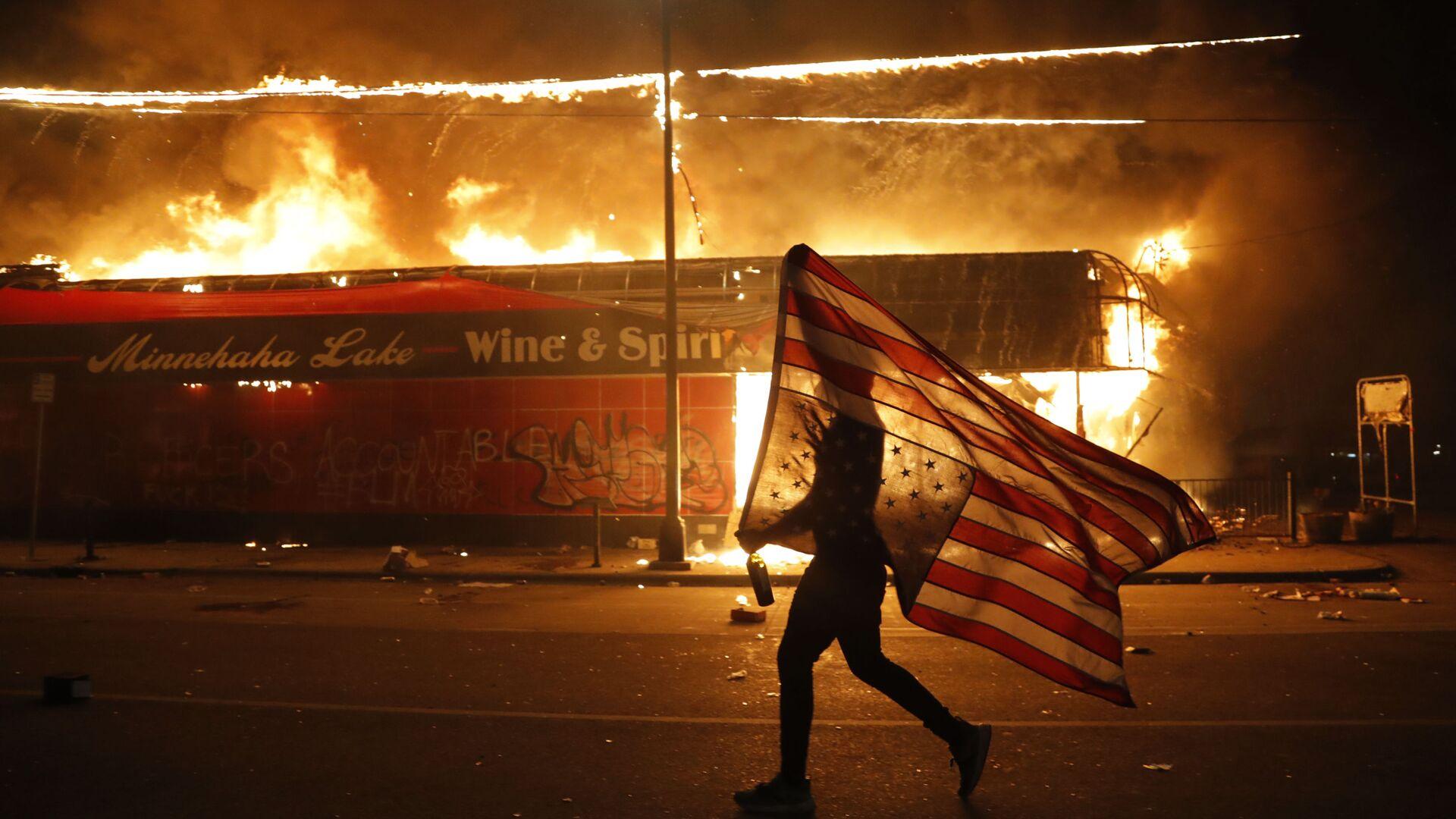 Un manifestante porta la bandera de EEUU boca abajo como símbolo de peligro extremo que vive el país frente un edificio en llamas en Minneapolis (estado de Minnesota), durante las protestas causadas por la muerte de George Floyd, el 28 de mayo del 2020 - Sputnik Mundo, 1920, 28.06.2021