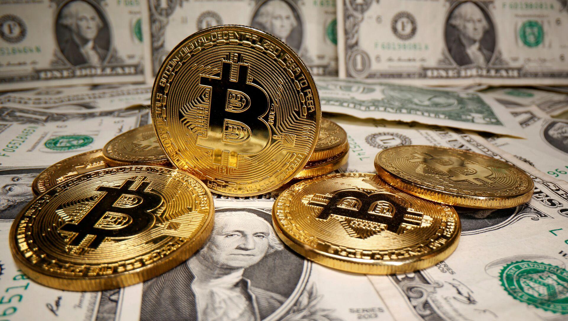 Monedas con el logo del bitcoin y dólares estadounidenses (imagen referencial) - Sputnik Mundo, 1920, 22.01.2021