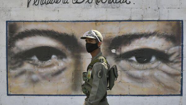 Un soldado frente al mural con los ojos de Hugo Chávez en Caracas, Venezuela - Sputnik Mundo