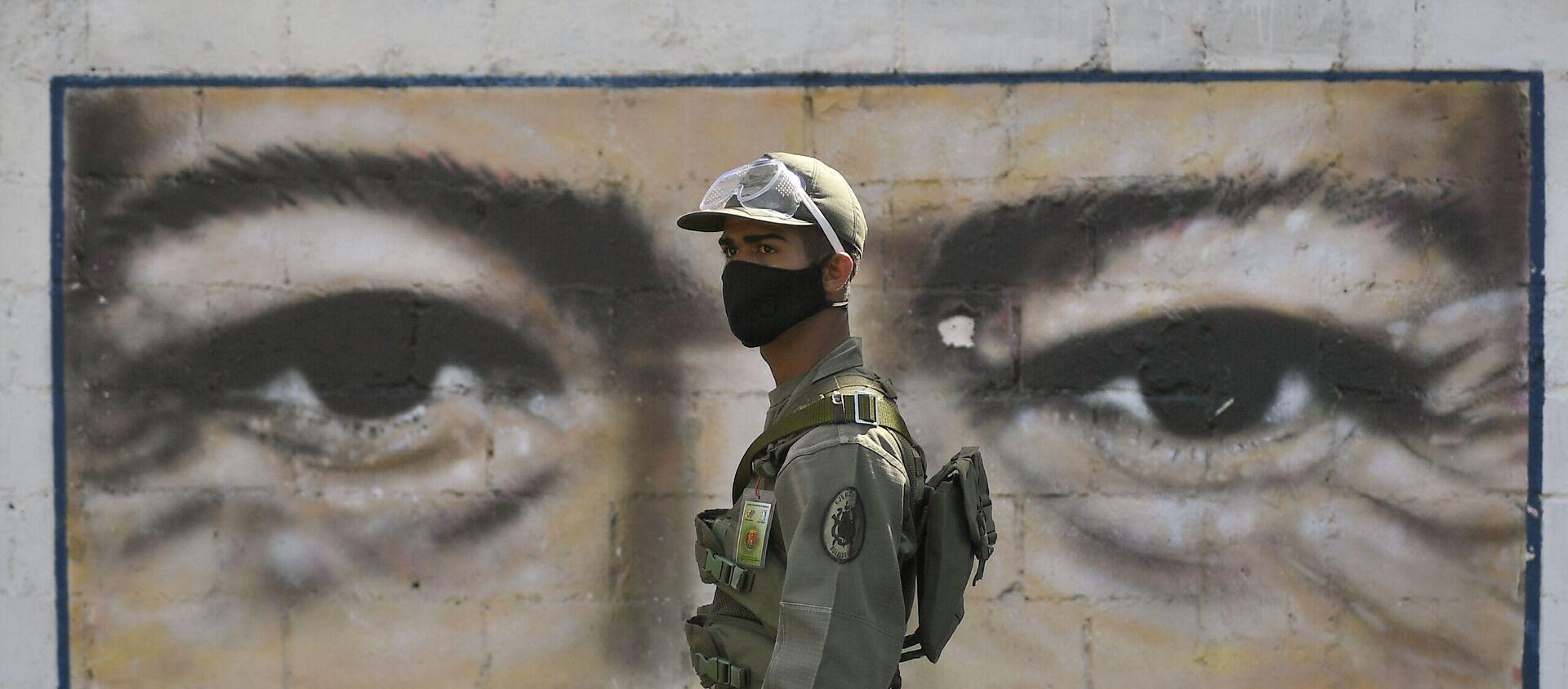 Un soldado frente al mural con los ojos de Hugo Chávez en Caracas, Venezuela - Sputnik Mundo, 1920, 05.01.2021