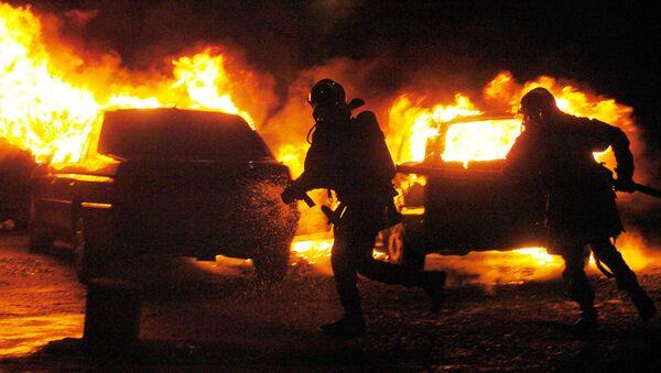 Bomberos intentan extinguir el fuego en autos prendidos por vándalos en los suburbios de Estrasburgo (Francia), el 1 de enero del 2005 - Sputnik Mundo