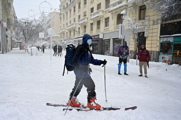 Una mujer utiliza esquíes para desplazarse por la nieve que cubre la capital de España. - Sputnik Mundo