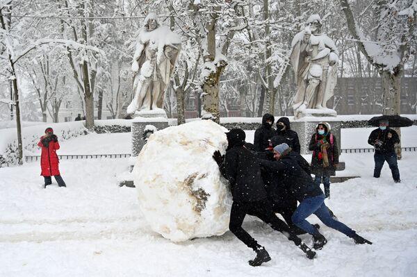 Unos jóvenes hacen una bola de nieve gigante en Madrid después de una fuerte nevasca. - Sputnik Mundo