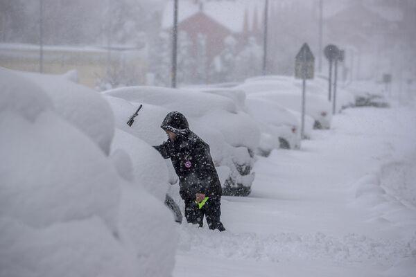 Un hombre quita la nieve de su automóvil durante una nevasca en Rivas Vaciamadrid. - Sputnik Mundo