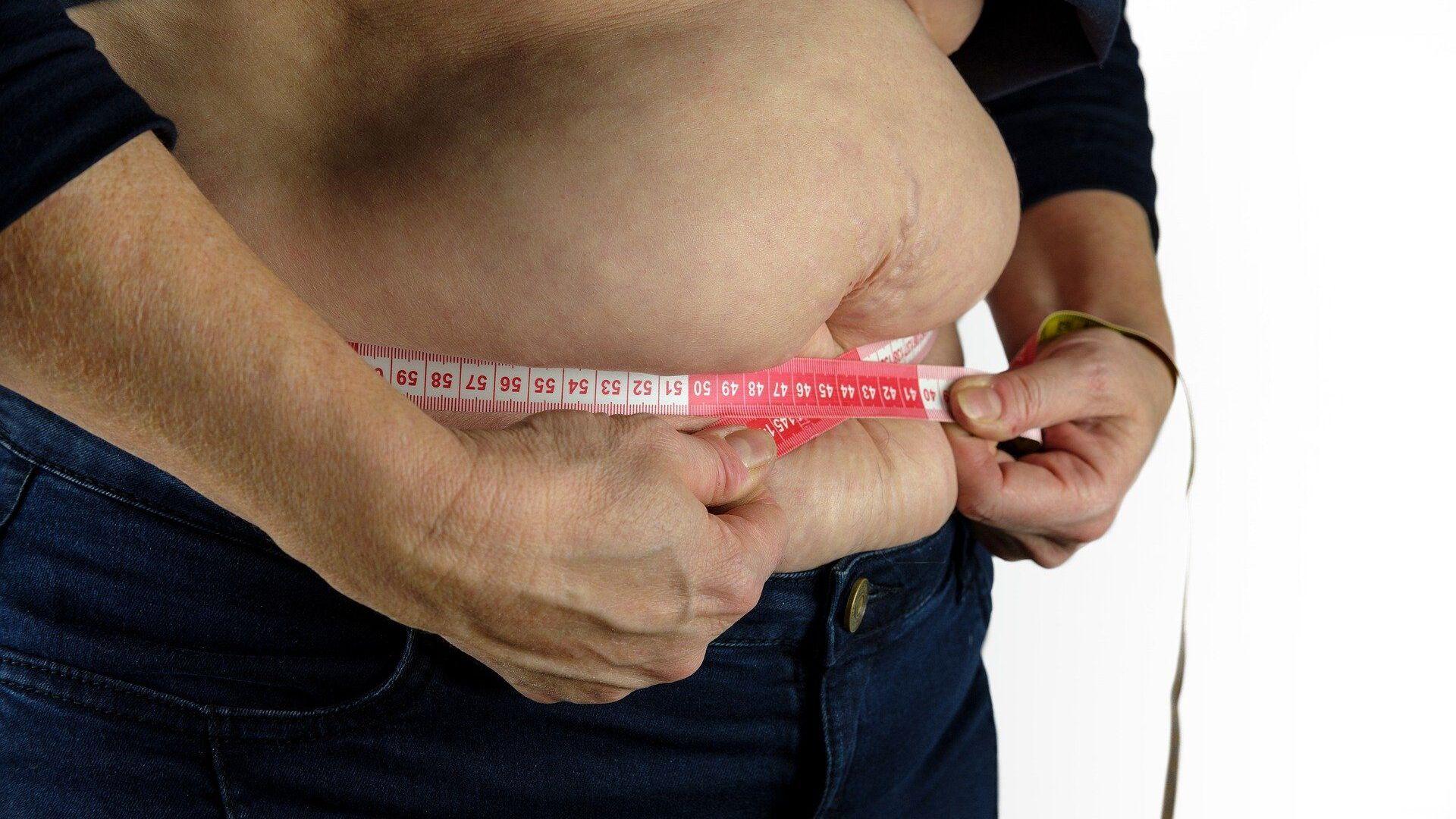 Una persona se mide la barriga con una cinta métrica - Sputnik Mundo, 1920, 11.01.2021