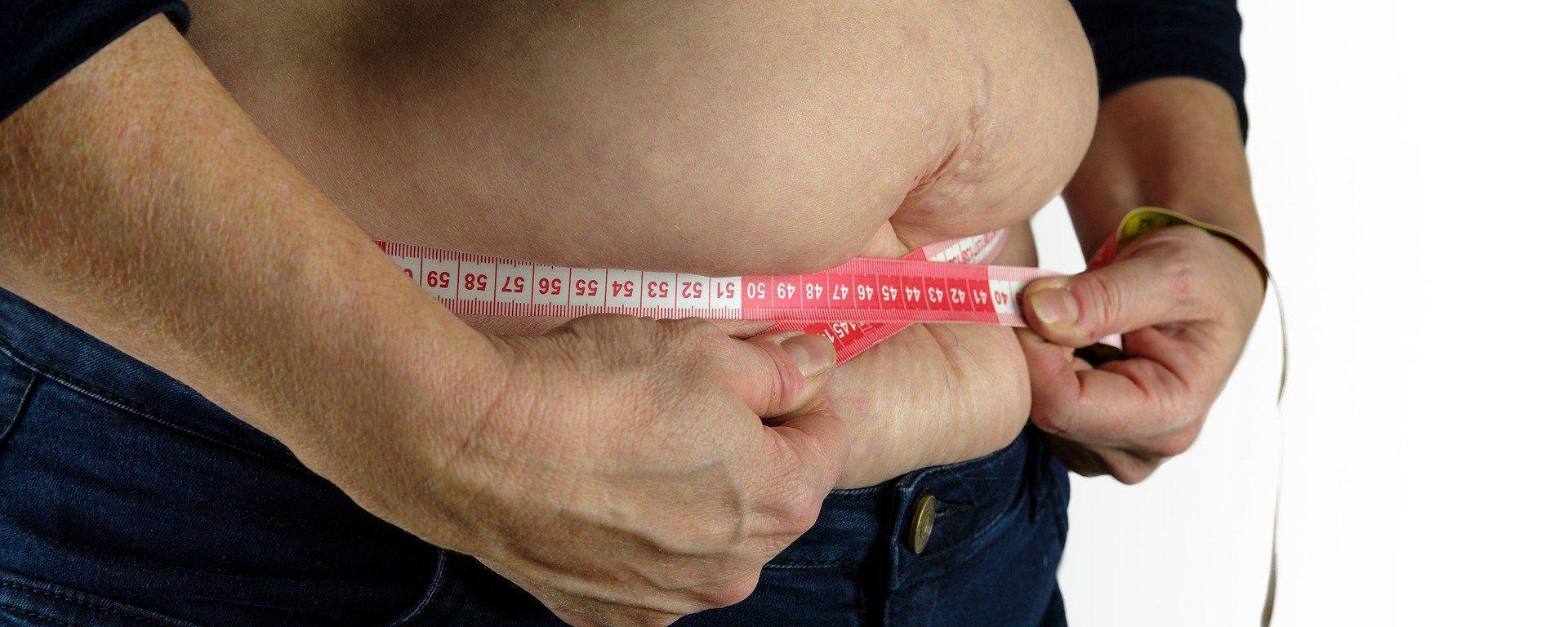 Una persona se mide la barriga con una cinta métrica - Sputnik Mundo, 1920, 28.02.2021