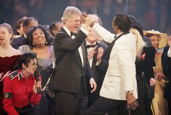 La primera toma de posesión de Bill Clinton como presidente de Estados Unidos se llevó a cabo el 20 de enero de 1993. Con poco más de 46 años en la ocasión, Clinton se convirtió en el tercer presidente más joven hasta aquel momento y el primer representante de la generación de los 'baby boomers'. En la foto: El presidente electo Bill Clinton choca los cinco con el cantante Chuck Berry, en la final de la Gala Presidencial, a pocos días de asumir el cargo más importante de la política de EEUU. A la izquierda, agachado, se ve a Michael Jackson. - Sputnik Mundo
