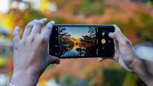 Una persona hace foto con su teléfono inteligente - Sputnik Mundo