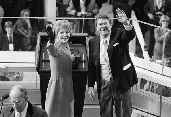 El republicano Ronald Reagan tomó la posesión como el 40.º presidente de EEUU el 20 de enero de 1981. La ceremonia de investidura fue la primera en realizarse en el Frente Occidental del Capitolio —el edificio del Congreso estadounidense—, en donde se realizan hasta los días actuales. A pocos días de cumplir 70 años en el momento de su investidura, Reagan se convirtió en la persona de mayor edad en asumir la presidencia de EEUU hasta aquel momento.En la foto: el presidente Ronald Reagan y la primera dama Nancy Reagan saludan a los espectadores en el edificio del Capitolio luego de la ceremonia de toma de posesión, el 20 de enero de 1981. - Sputnik Mundo