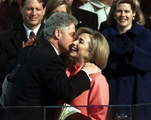 Pese al escándalo Lewinsky en 1998, lo cual culminó en un intento fallido de destituir a Clinton de la Presidencia, el demócrata logró reelegirse. Su segunda ceremonia de toma de posesión, el 20 de enero de 1997, fue la primera en transmitirse en directo por internet.En la foto: el presidente Bill Clinton besa a su esposa, Hillary Clinton, después de jurar su segundo mandato.  - Sputnik Mundo