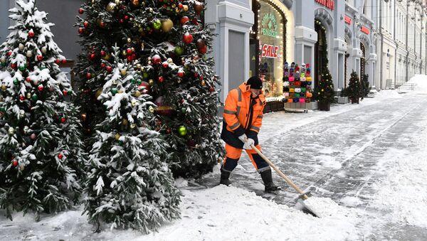 Un trabajador limpia de nieve una calle de Moscú  - Sputnik Mundo