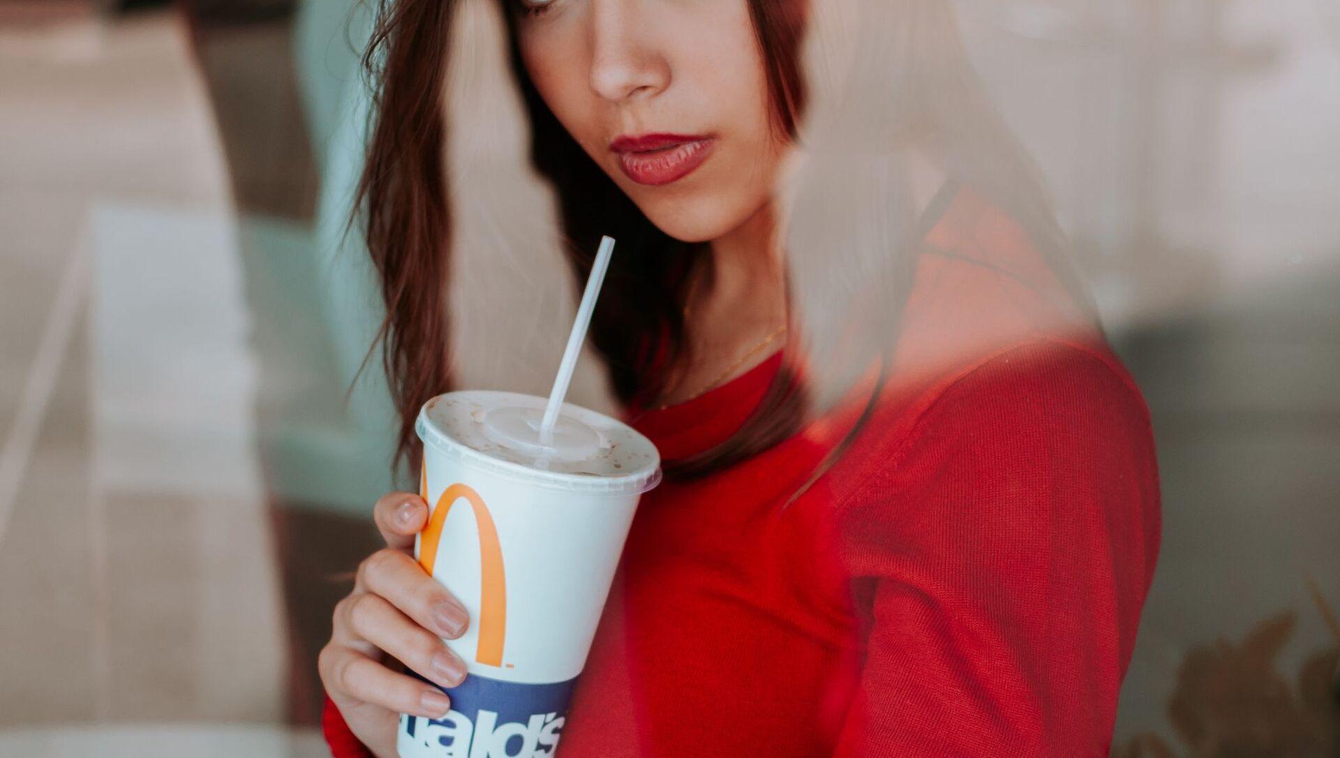 Una mujer con un vaso de Coca-Cola de McDonald's - Sputnik Mundo, 1920, 14.01.2021