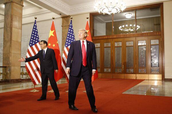 En la escena internacional, Trump ha luchado activamente por el dominio de EEUU y por romper el sistema habitual de controles y equilibrios. Uno de sus principales 'logros' en esta área fue desatar una guerra comercial con China. En la foto: Donald Trump y el primer ministro chino, Li Keqiang, durante una reunión en Pekín, noviembre de 2017.   - Sputnik Mundo