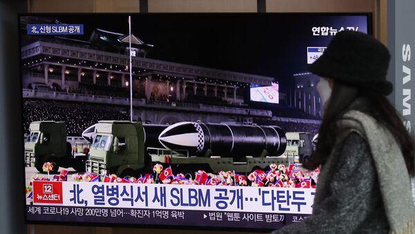 Una mujer ve por la televisión el desfile militar celebrado en Pyongyang  - Sputnik Mundo