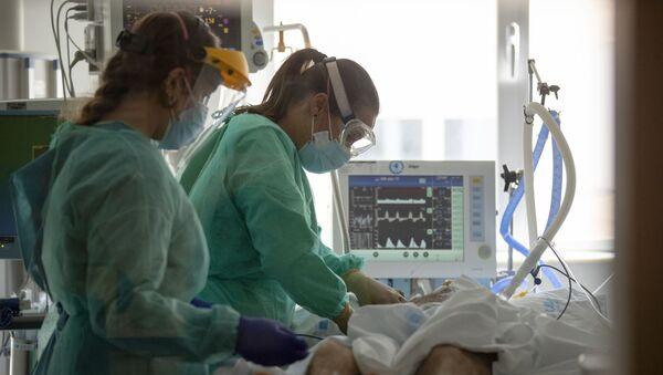 Trabajadores sanitarios asisten a un paciente con COVID-19 en una de las unidades de cuidados intensivos (UCI) del Hospital Universitario de Torrejón - Sputnik Mundo