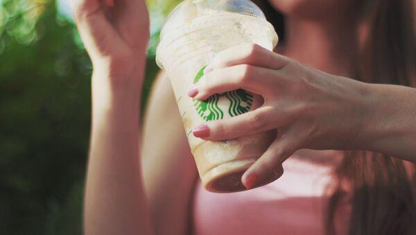Una joven con un café de Starbucks - Sputnik Mundo