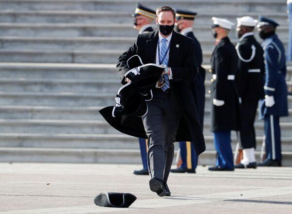 Funcionarios de la Administración recogen los sombreros caídos tras la toma de posesión del 46 presidente de Estados Unidos, Joe Biden.   - Sputnik Mundo