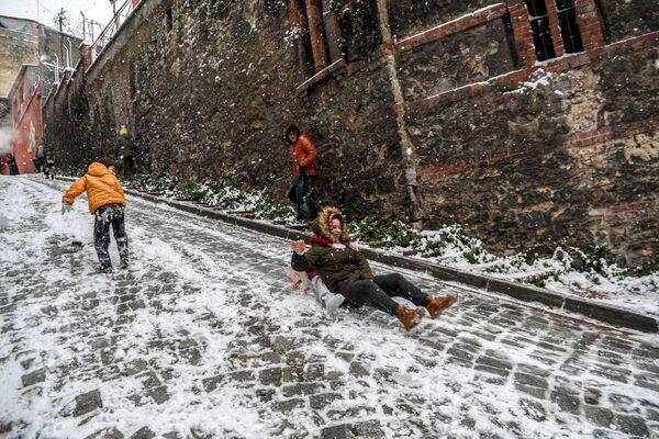 Unos niños se deslizan en una calle de la ciudad de Estambul cubierta de nieve.  - Sputnik Mundo