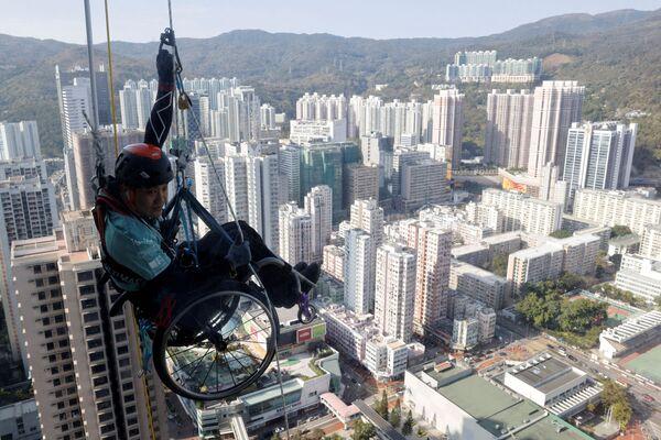 El alpinista Lai Chi-wai, que padece una parálisis de las extremidades inferiores, intenta escalar la torre Nina en Hong Kong. - Sputnik Mundo