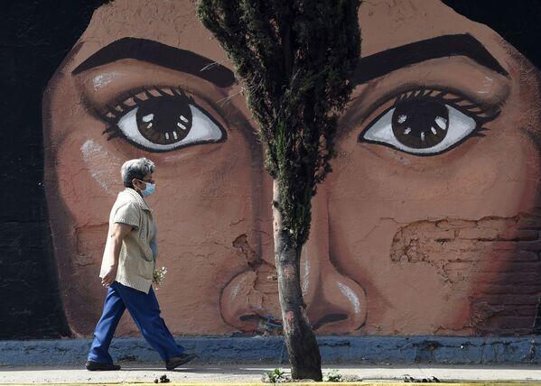 Una mujer pasa cerca del grafiti de una de las paredes del cementerio San Nicolás Tolentino en el municipio Iztapalapa, en México.  - Sputnik Mundo