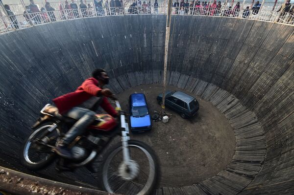 Un doble de acción realiza un truco en el espectáculo 'Pared de la Muerte' en una feria en Allahabad, India. - Sputnik Mundo