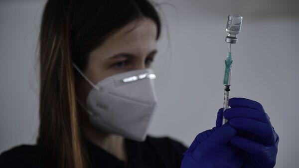 Imagen referencial de una sanitaria suministrando la vacuna de Pfizer en España - Sputnik Mundo