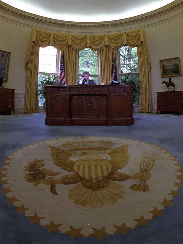 Las cortinas y la alfombra utilizadas en el despacho Oval por Bill Clinton durante sus ocho años al mando de EEUU son las mismas que utiliza ahora Biden.En la foto: Clinton habla por teléfono en el Despacho Oval (1993). - Sputnik Mundo