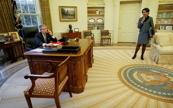 George W. Bush, entre otras cosas, agregó un busto del primer ministro británico Winston Churchill a la decoración del Despacho Oval. La escultura volvió a la oficina presidencial años más tarde, durante el mandato de Trump.En la foto: el presidente Bush habla por teléfono desde el Despacho Oval. A la derecha, Condoleezza Rice, secretaria de Estado de los Estados Unidos (2003). - Sputnik Mundo