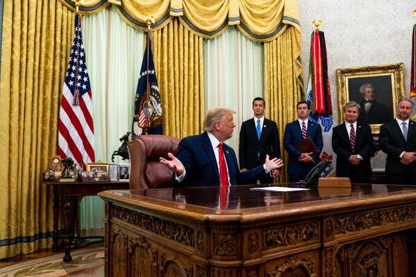 Durante sus cuatro años en la presidencia, Trump mantuvo las banderas de las ramas militares de EEUU en el Despacho Oval. Los pabellones se removieron de la decoración con la llegada de Biden al poder.En la foto: Trump se dirige a periodistas en la Oficina Oval de la Casa Blanca (2020).  - Sputnik Mundo