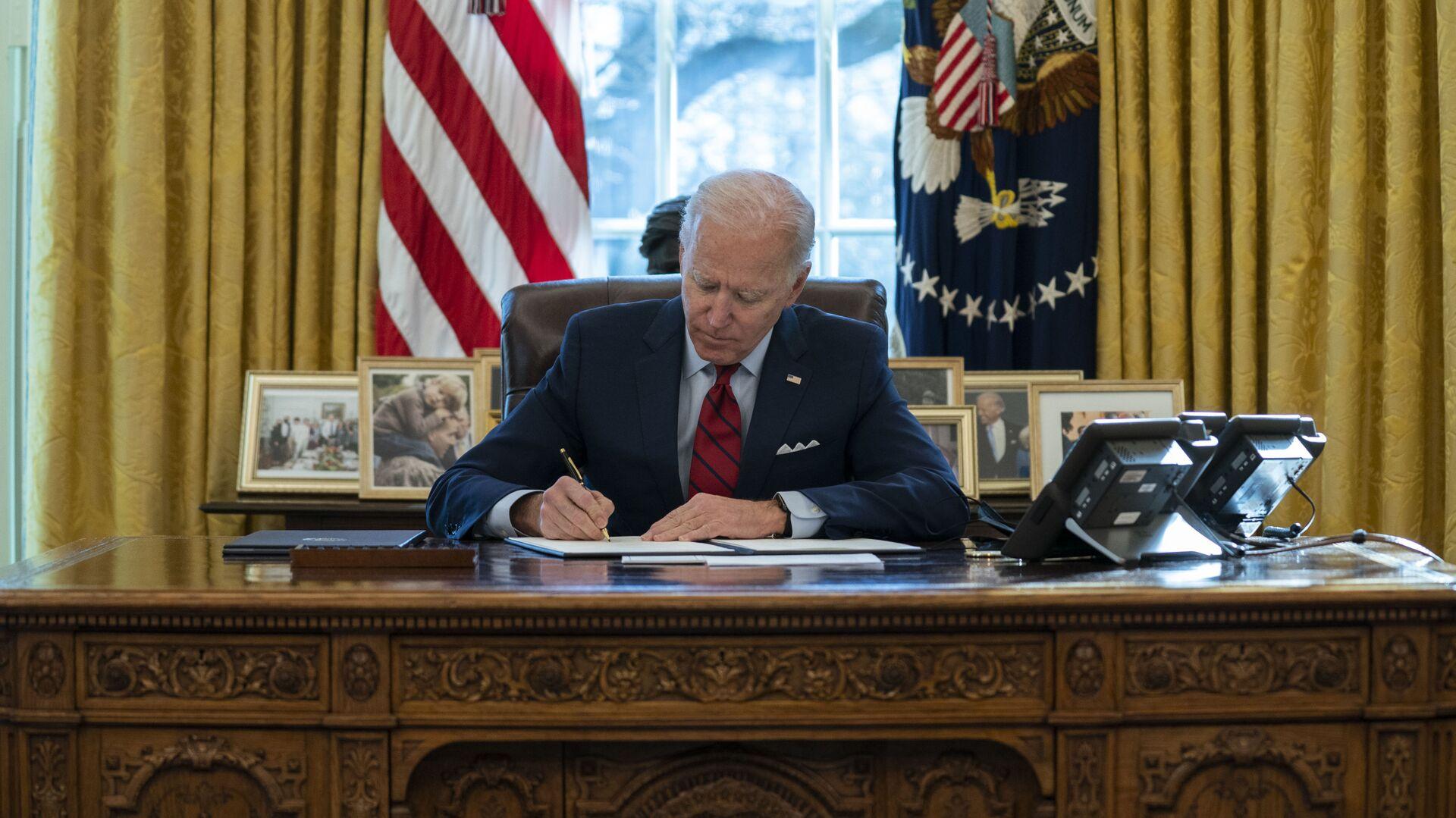 Joe Biden, presidente de EEUU, firma varios documentos ejecutivos en el Despacho Oval de la Casa Blanca, en Washington, el 28 de enero del 2021 - Sputnik Mundo, 1920, 11.03.2021