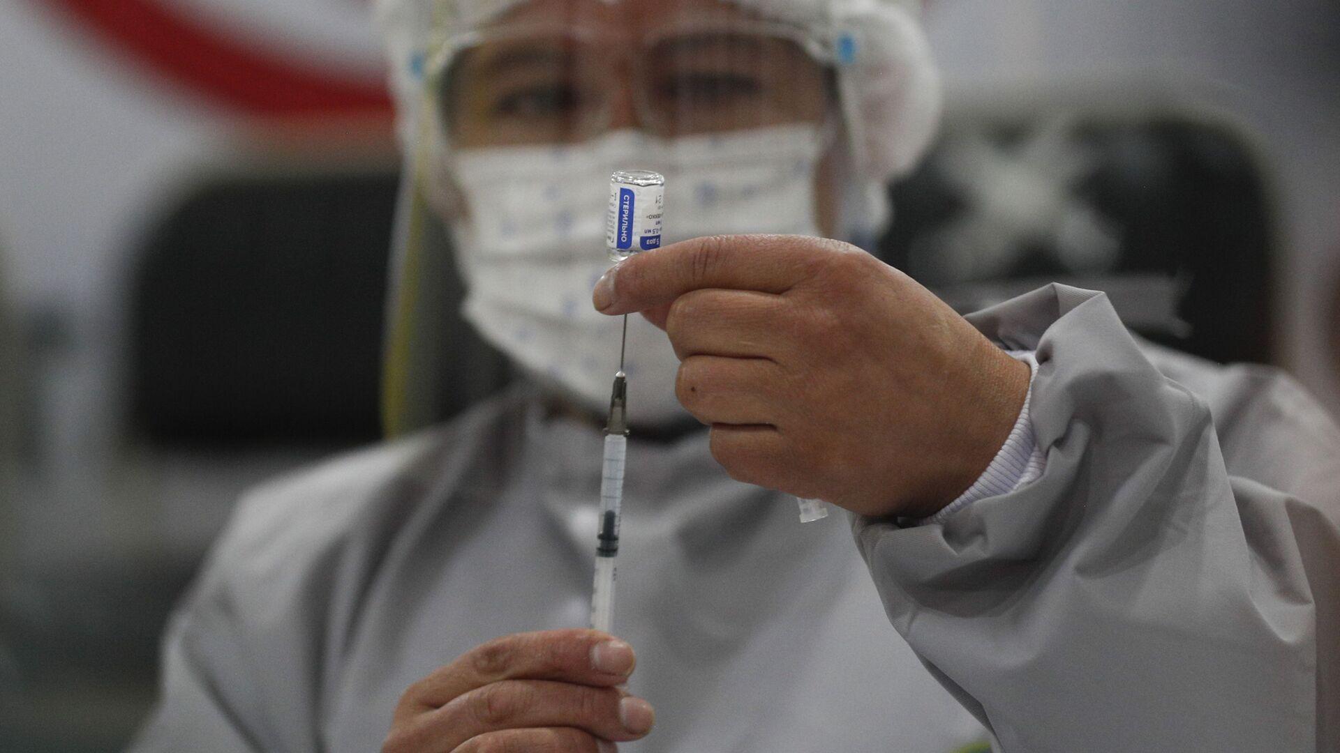 Un trabajador de la salud prepara una dosis de la vacuna rusa Sputnik V COVID-19, en el Hospital Del Norte en El Alto, Bolivia - Sputnik Mundo, 1920, 11.03.2021