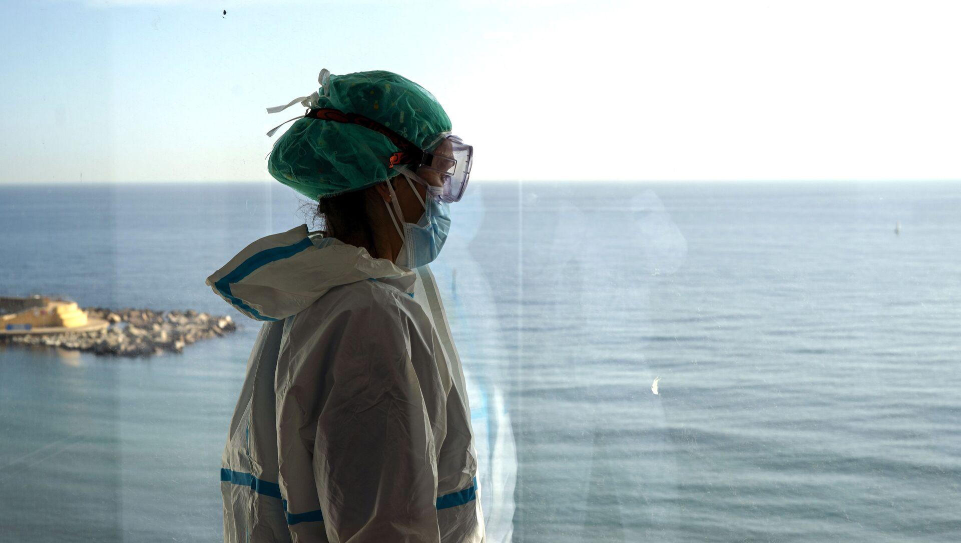 La enfermera Marta Fernández mira el mar desde una ventana durante un breve descanso en la sala COVID-19 del hospital del Mar en Barcelona - Sputnik Mundo, 1920, 02.02.2021