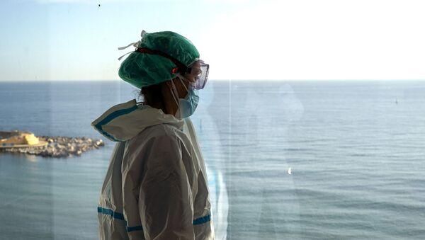 La enfermera Marta Fernández mira el mar desde una ventana durante un breve descanso en la sala COVID-19 del hospital del Mar en Barcelona - Sputnik Mundo