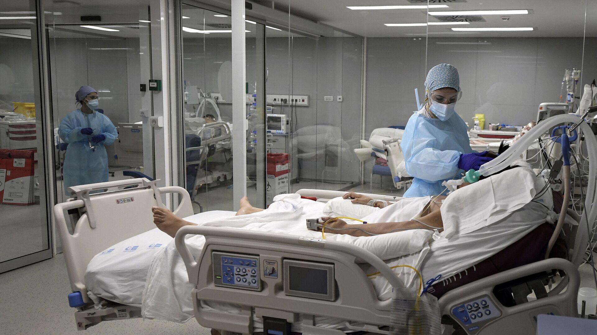Una enfermera cuida de un paciente en el Hospital Zendal de Madrid - Sputnik Mundo, 1920, 02.02.2021