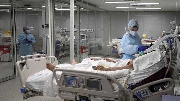 Una enfermera cuida de un paciente en el Hospital Zendal de Madrid - Sputnik Mundo