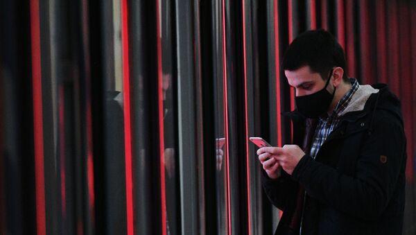 Una persona en mascarilla con un teléfono móvil (referencial) - Sputnik Mundo