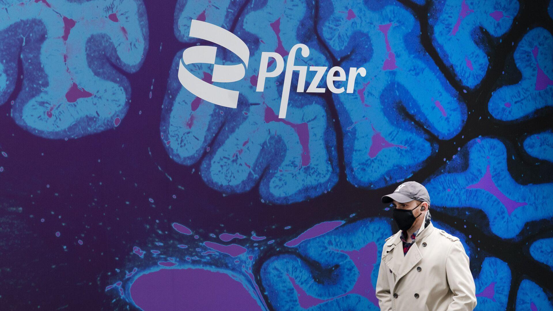 Un hombre camina frente a un logo del laboratorio de Pfizer frente a la sede del laboratorio en Nueva York - Sputnik Mundo, 1920, 25.02.2021