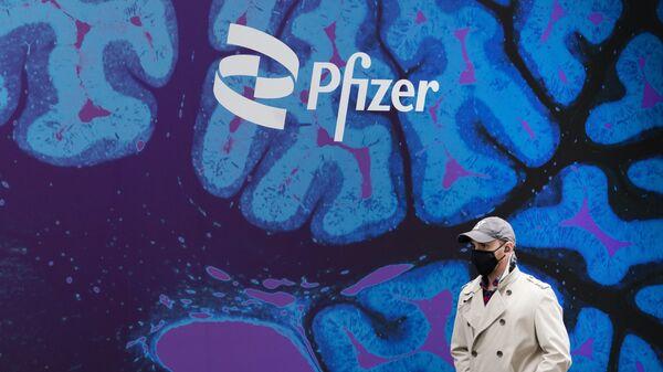 Un hombre camina frente a un logo del laboratorio de Pfizer frente a la sede del laboratorio en Nueva York - Sputnik Mundo