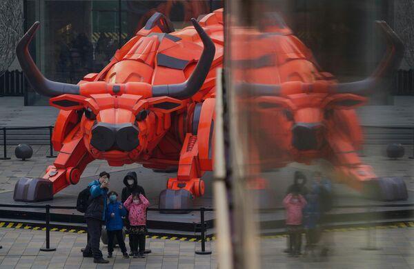 Durante el Año Nuevo lunar —más conocido como la Fiesta de la Primavera en China— Pekín ha prohibido los fuegos artificiales y los petardos. En esta foto: una familia frente a una escultura de un toro en un centro comercial de Pekín en vísperas del Año Nuevo lunar. - Sputnik Mundo