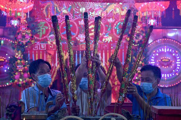 Los creyentes con palitos aromatizantes en un templo durante el Año Nuevo lunar en Ta Khmau, Camboya. - Sputnik Mundo