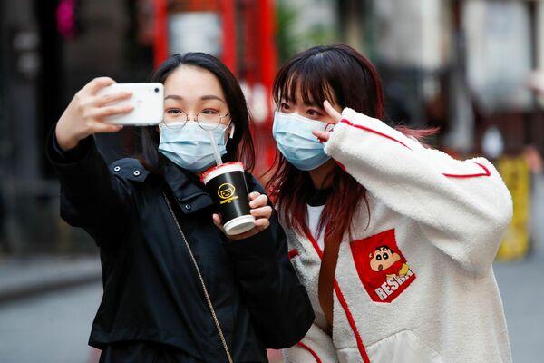Unas muchachas se toman selfies en el barrio chino de Londres en vísperas del Año Nuevo lunar. - Sputnik Mundo