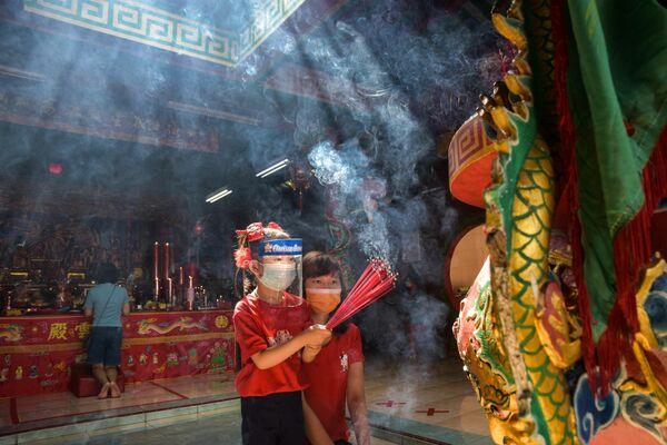 En Indonesia, están prohibidos los eventos familiares y se cancelaron los festivales. El país está experimentando un nuevo brote de la enfermedad, con más de 10.000 casos diarios de contagio. En total, hay más de un millón de casos en Indonesia y 32.000 muertes por el coronavirus. En la foto: niñas con máscaras protectoras y palitos aromatizantes durante la celebración del Año Nuevo lunar en un templo de Indonesia. - Sputnik Mundo
