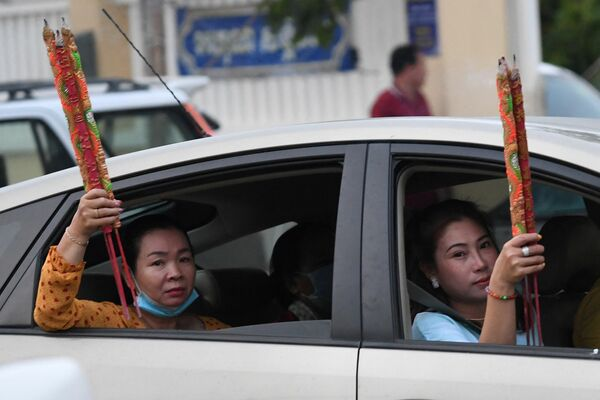 Unas mujeres con palitos aromatizantes en un coche durante la celebración del Año Nuevo lunar en Ta Khmau, Camboya. - Sputnik Mundo