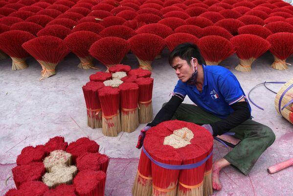 Un hombre empaca palitos aromatizantes cerca de Hanói, Vietnam. - Sputnik Mundo