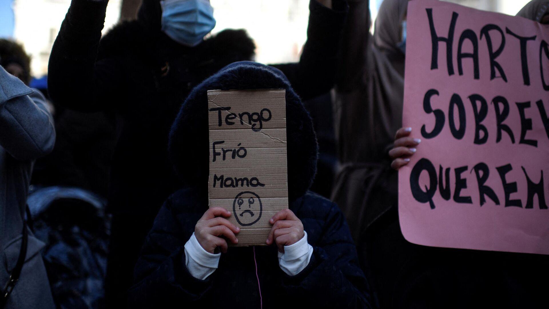 Una niña lleva un cartón que dice Tengo frío, mamá durante una manifestación contra los cortes de luz frente a la sede del gobierno regional en Madrid. 3 de diciembre de 2020. - Sputnik Mundo, 1920, 16.02.2021